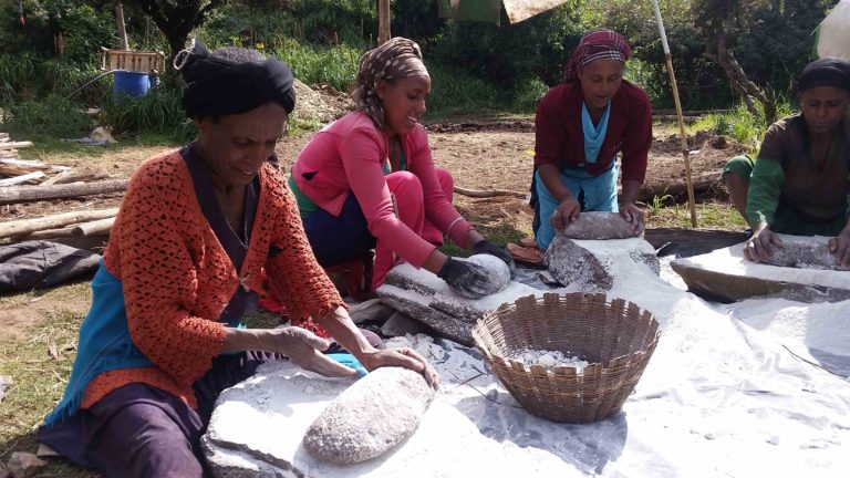Some women of the community mill with the millstones (not flour but chalk for the wall paints).